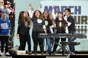 "WASHINGTON, DC - MARCH 24: Marjory Stoneman Douglas High School drama club and choir members perform ""Shine"" during the March for Our Lives rally on March 24, 2018 in Washington, DC. Hundreds of thousands of demonstrators, including students, teachers and parents gathered in Washington for the anti-gun violence rally organized by survivors of the Marjory Stoneman Douglas High School shooting on February 14 that left 17 dead. More than 800 related events are taking place around the world to call for legislative action to address school safety and gun violence. (Photo by Chip Somodevilla/Getty Images)"