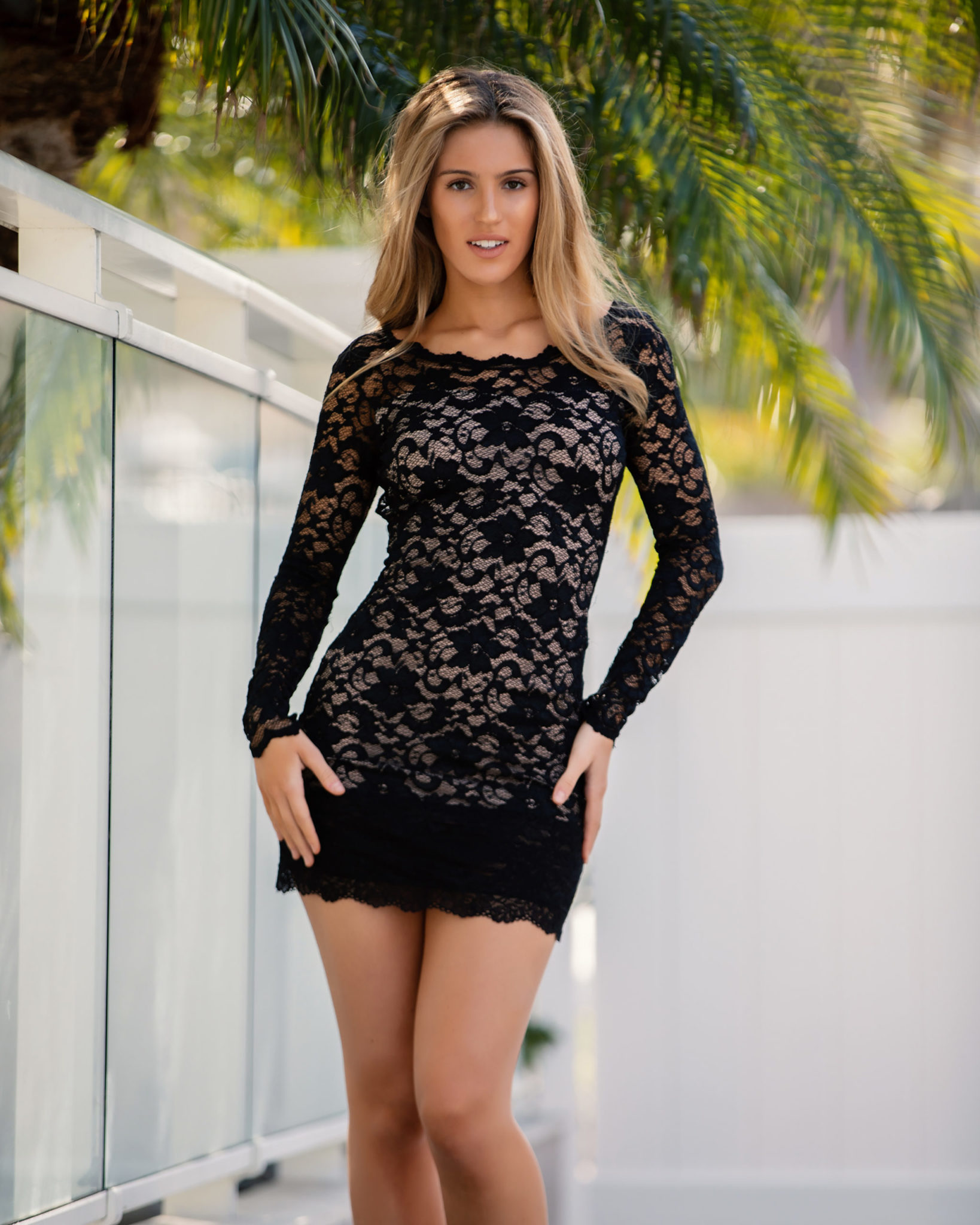Back in black: This form-fitting, feminine piece in stretch lace material features a boat-shaped neck in front and a deep cut in the back; the dress is finished around the edges with lace scallops. (Model: Chloe Leonik)