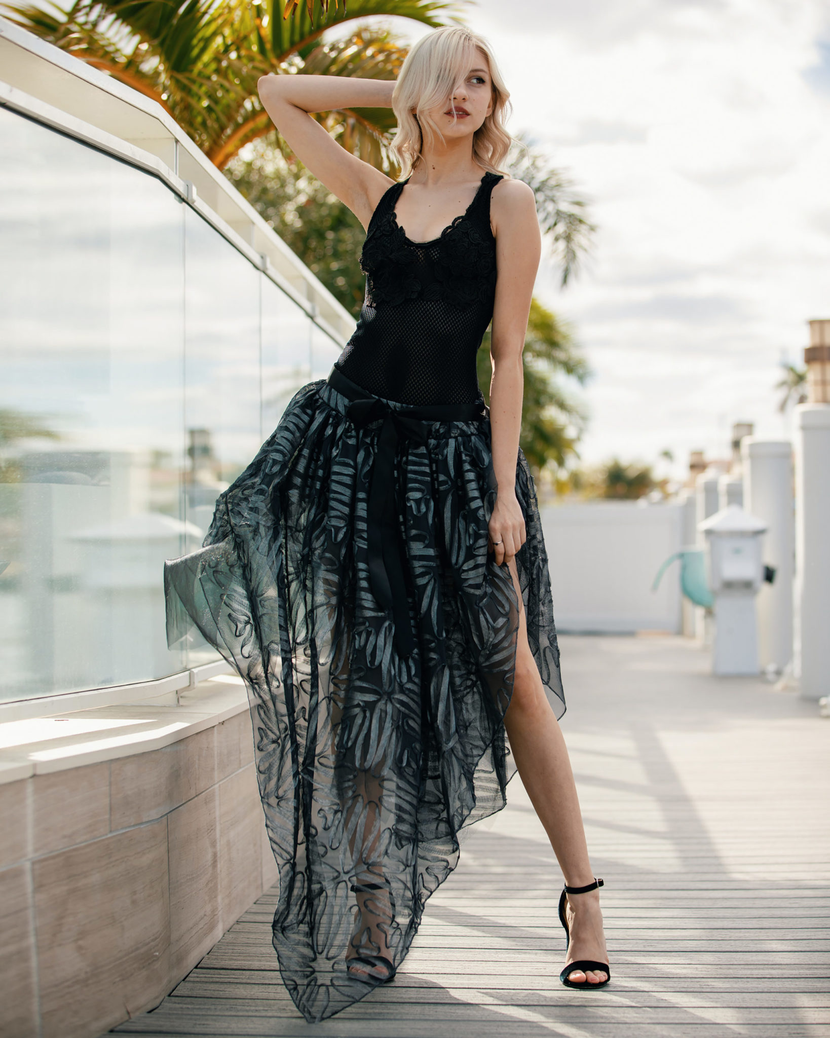 Sheer beauty: A double-layer handkerchief skirt, designed in a lush 3D pattern of silver tones and illusion threads, pairs seamlessly with a black body suit that's enhanced by beaded Chantilly fabric flower details. (Model: Ashley Van Helden)
